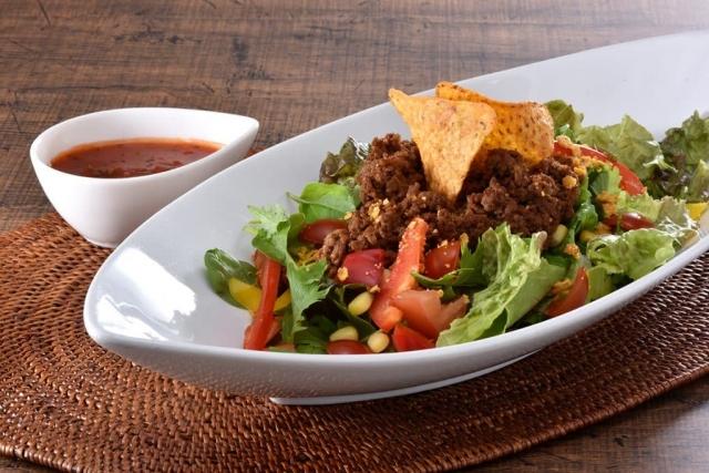 ライスの上にたっぷりなフレッシュ野菜とスパイシーな合い挽肉、チーズ、タコスなどをトッピング。